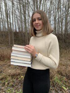 Alexandra Andersson står utomhus med en trave böcker i händerna.