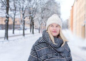 Porträttbild av Annelie Drewsen i stadsmiljö med snö på marken.