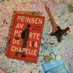 """Boken """"Prinsen av Porte de la Chapelle"""" ligger på en karta av Paris. Bredvid ligger några euro och ett metrokort. Ett litet Eiffeltorn står också på kartan."""