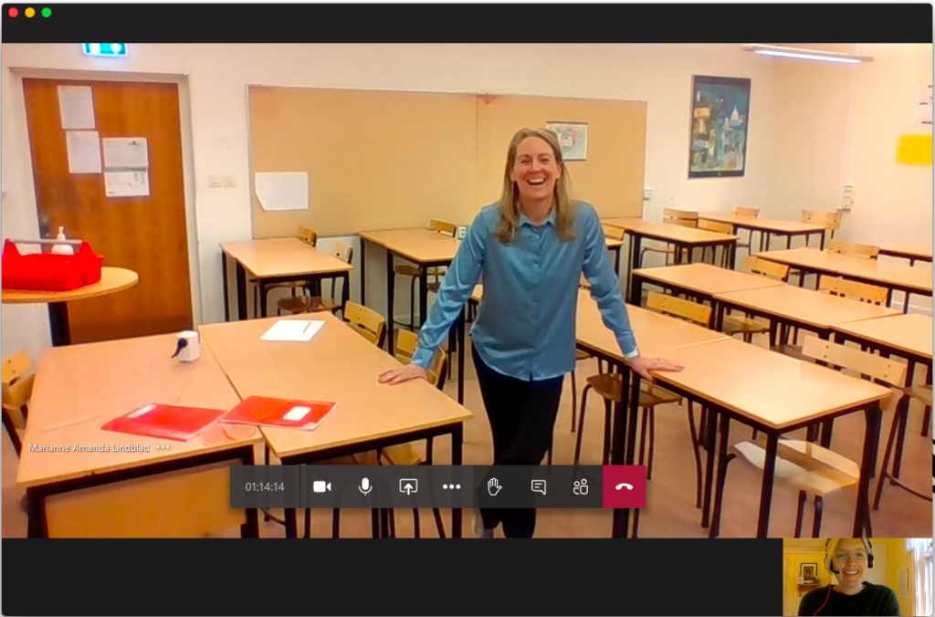 En lärare i ett tomt klassrum på en stor videobild, samt Annelie Drewsen med hörlurar på en mindre videobild. Skärmdump från videomöte.