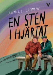 """Omslaget till """"En sten i hjärtat"""". Två äldre män sitter på en bänk och rör vid varandra. Bakgrunden är regnbågsfärgad."""